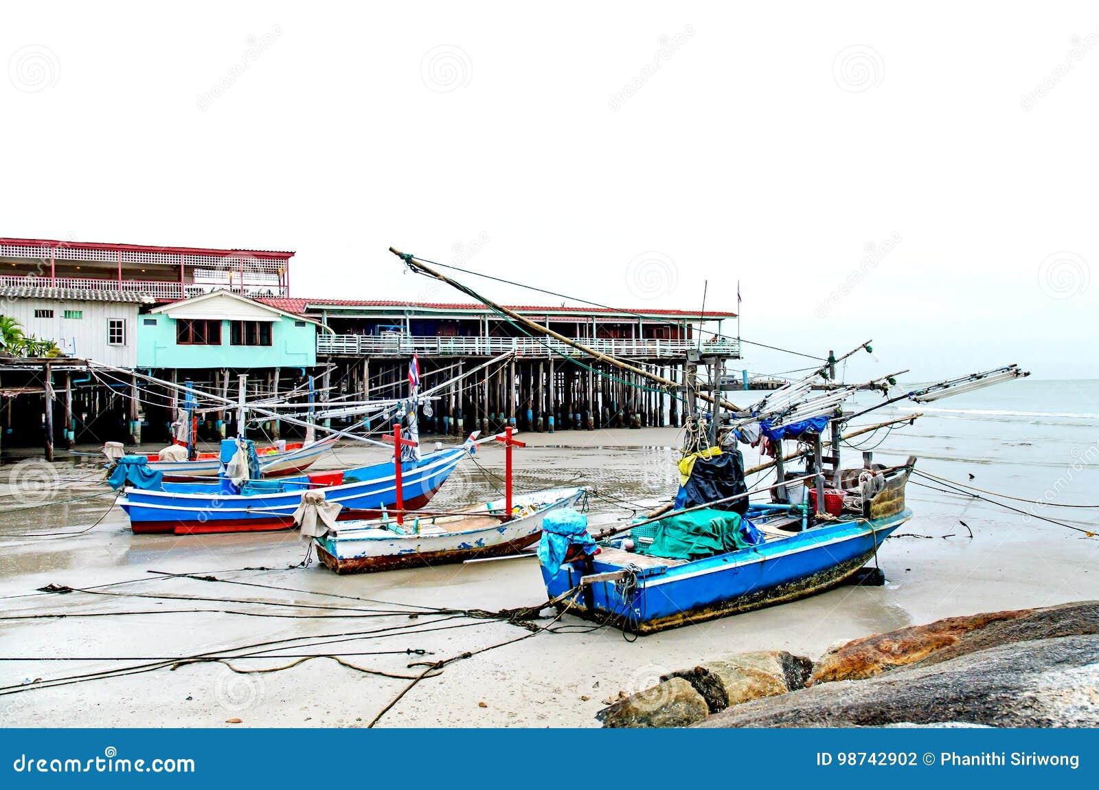Det sandstranden och havet med fiskebåten, som parkerade på det beachfront med, vaggar