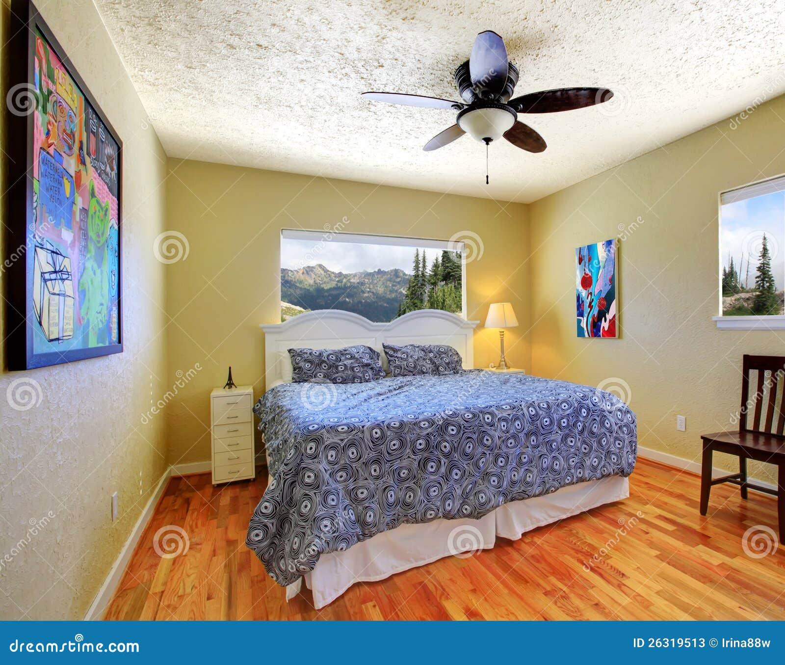 Det små sovrummet med gula väggar, berg beskådar, och grå färg ...