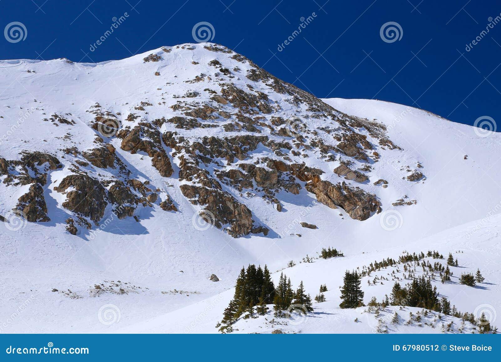 Det snöig steniga berget i vinter med blå himmel och vaggar