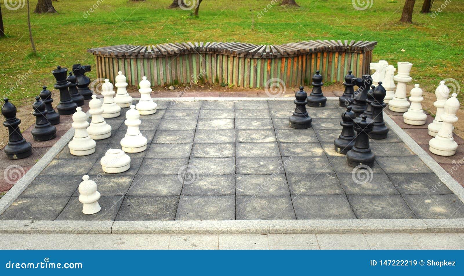 Det stora schackbrädet med enorma stycken i parkerar