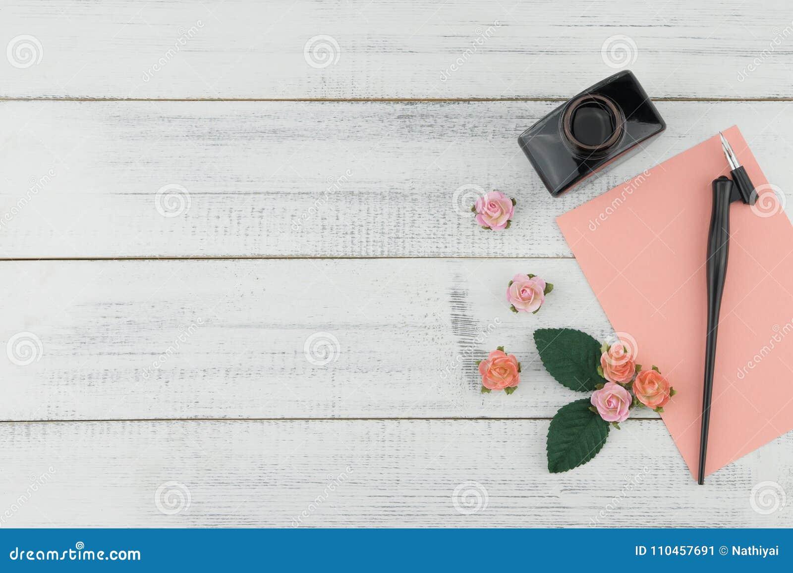 Det tomma rosa kortet, den sneda pennan och flaskan av färgpulver dekorerar med pappers- blommor för rosa färgrosen