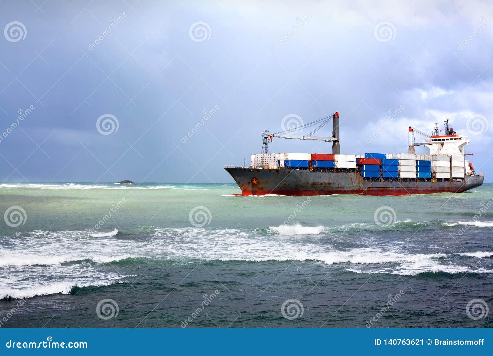 Det torra lastfartyget, skytteln för bäraren i stora partier med behållare ombord skriver in havshamnen i en hamnstad