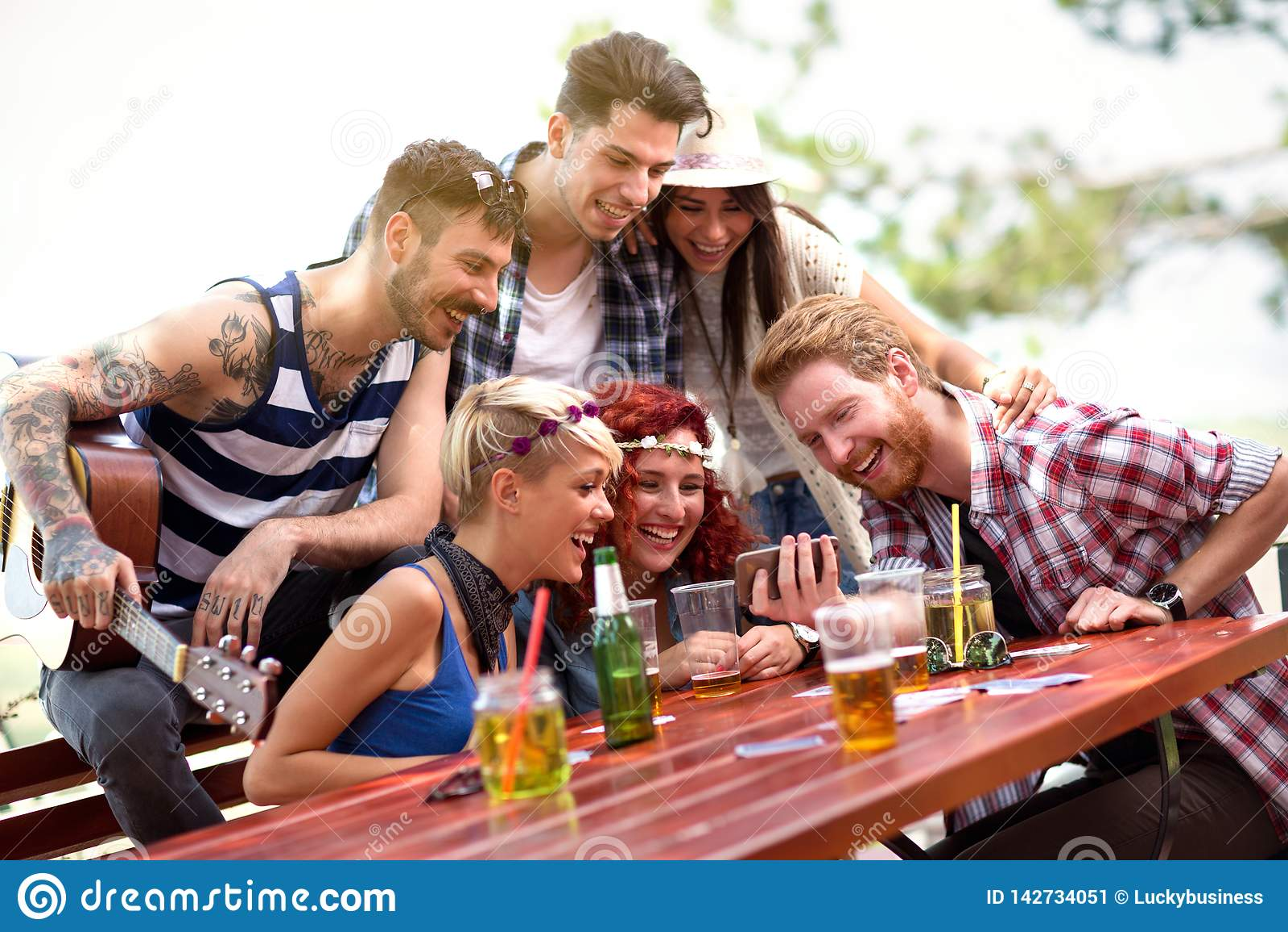 Det unga laget skrattar, medan hålla ögonen på deras foto på mobiltelefonen