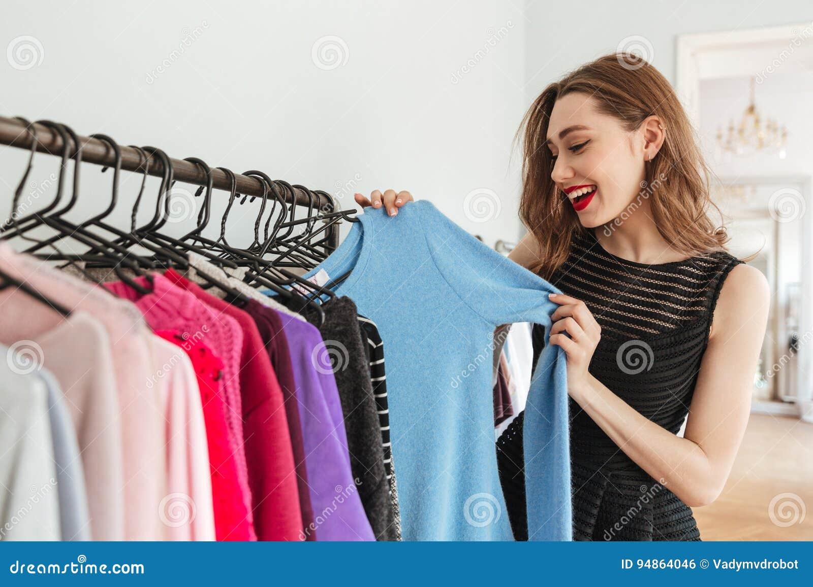 Det unga nätta kvinnaanseendet shoppar in välja inomhus kläder