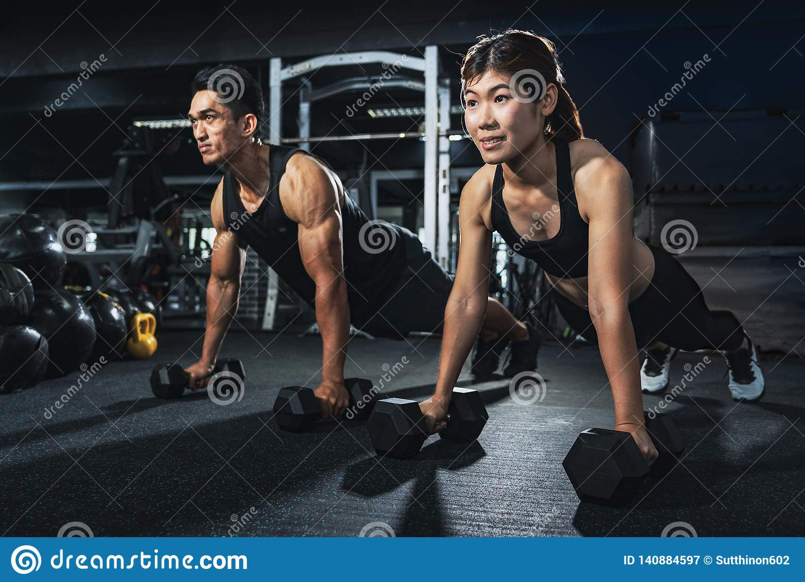 Det unga paret utarbetar på idrottshallen Den attraktiva kvinnan och den stiliga muskulösa mannen utbildar i ljus modern idrottsh