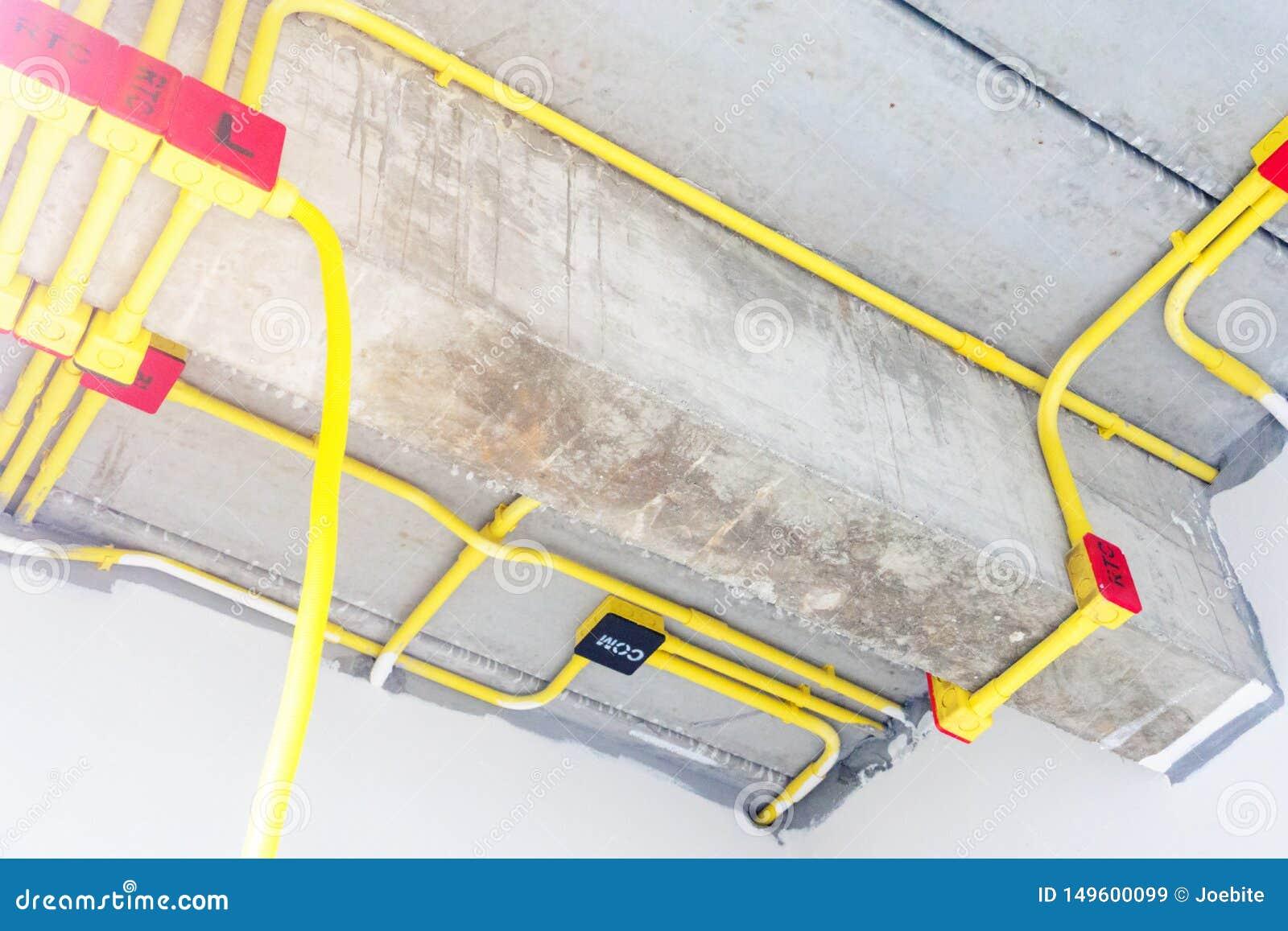 Det vita elektriska PVC-r?ret i r?tt och svart f?rbinds till kraftledningar eller elektriska tr?dar, EthernetUTP kablar, internet