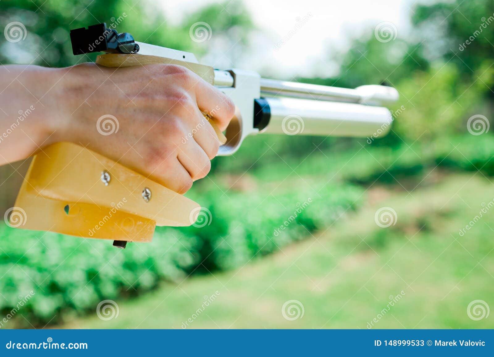 Detail die op hand naar maat gemaakte greep van het pistool van de sportlucht houden