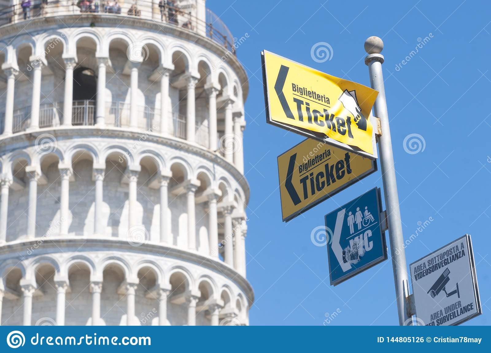 Detail of the leaning tower with directions to the ticket office, bathrooms and video surveillance notice