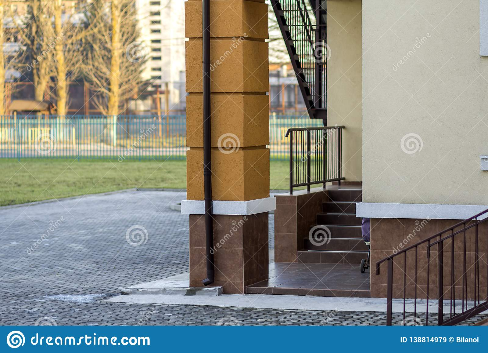 Detail of new kindergarten or school building corner with supporting column, staircase, metal fence and handrails on sunny