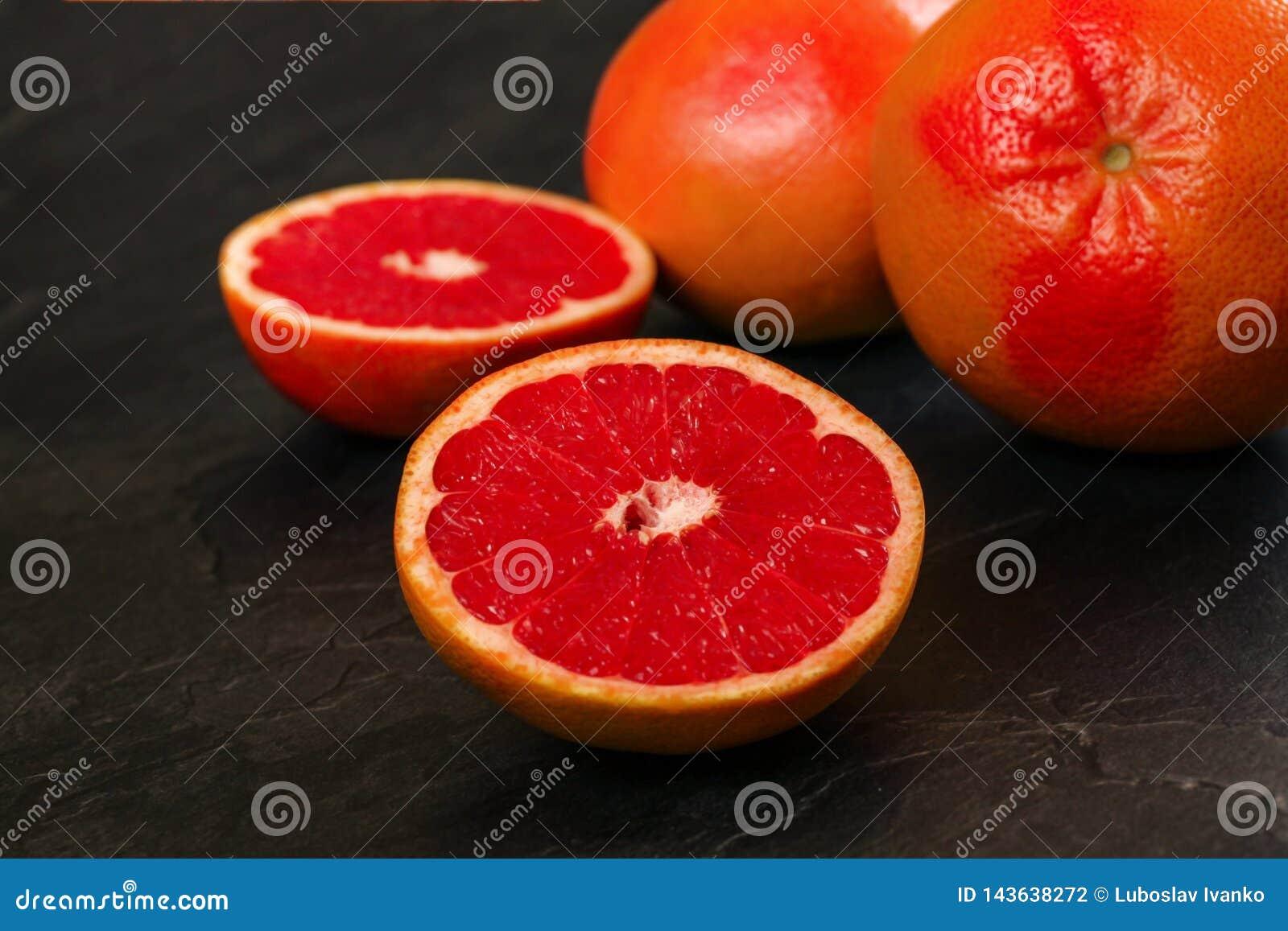 Detail of red grapefruit one citrus halved, on black slate like board