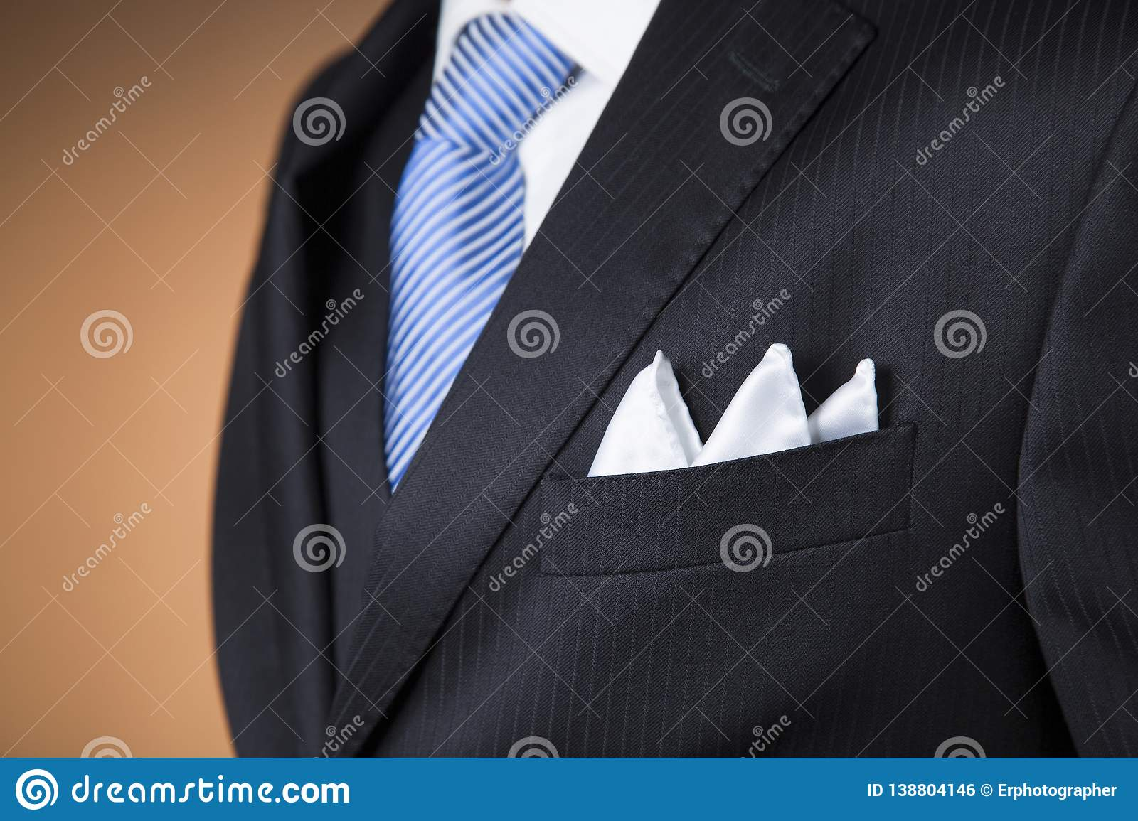 630c642e73b2f9 Close up of a white pocket handkerchief folded with three points in the  pocket of a black pinstripe suit with a blue tie and orange background