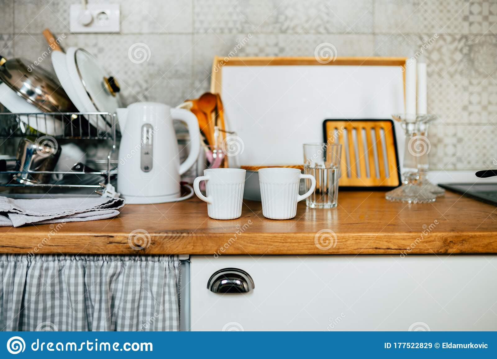Picture of: Detail Of Small Kitchen White Cupboards With Wooden Butchers Block Counter Top Two Cups In The Kitchen With Glassware And Dishes Stock Image Image Of Indoor Kitchenette 177522829