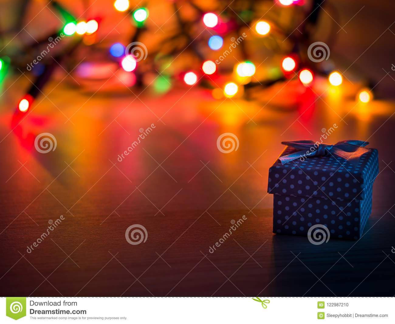 download detail of a tiny present and christmas lights in background stock photo image of