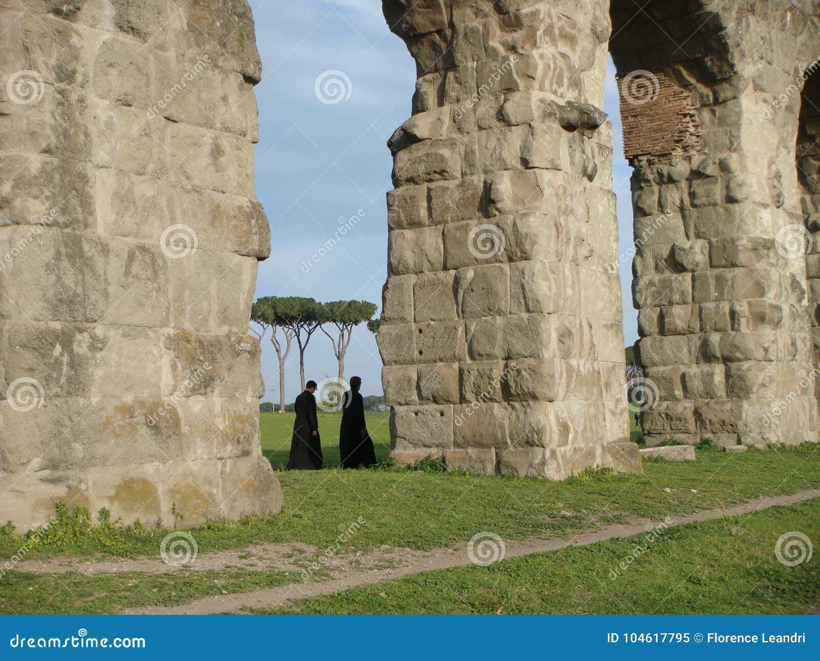Detail van bogen van een Roman aquaduct met in afstand twee lopende priesters rome Italië