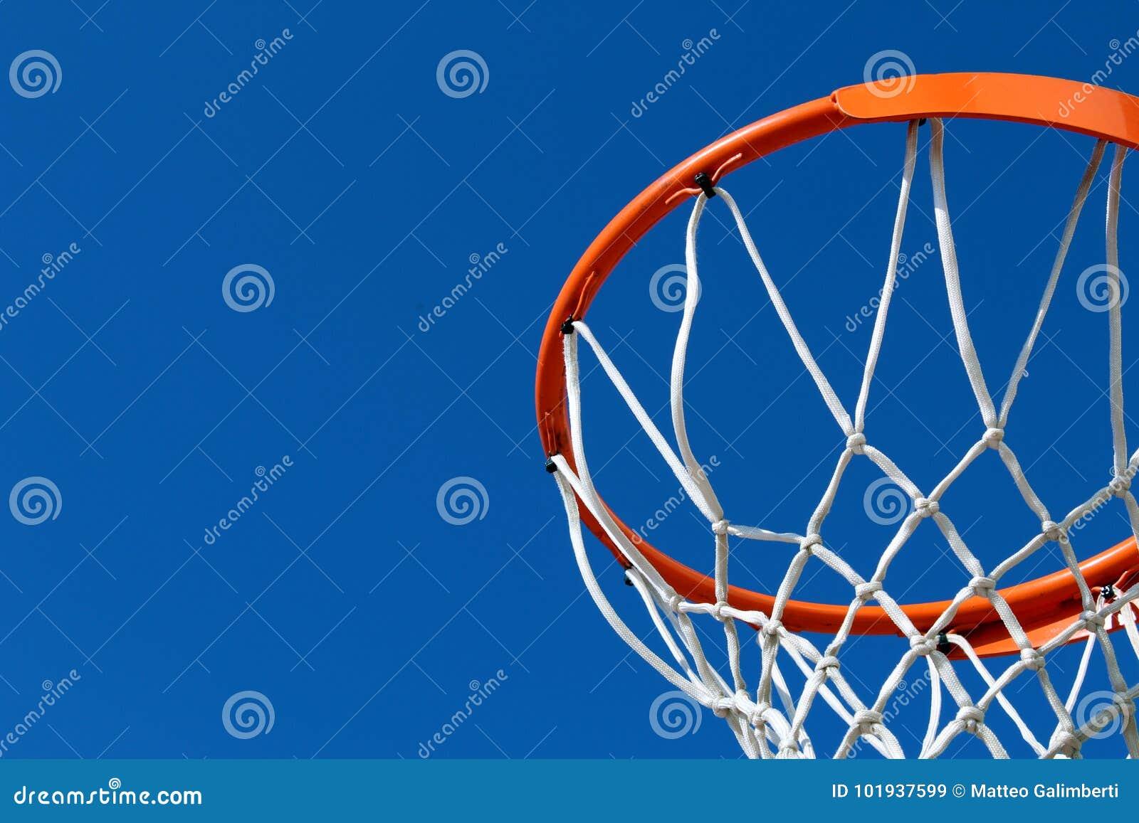 Detail van een oranje hoepel van de basketbalrand en witte netto tegen blauwe hemel