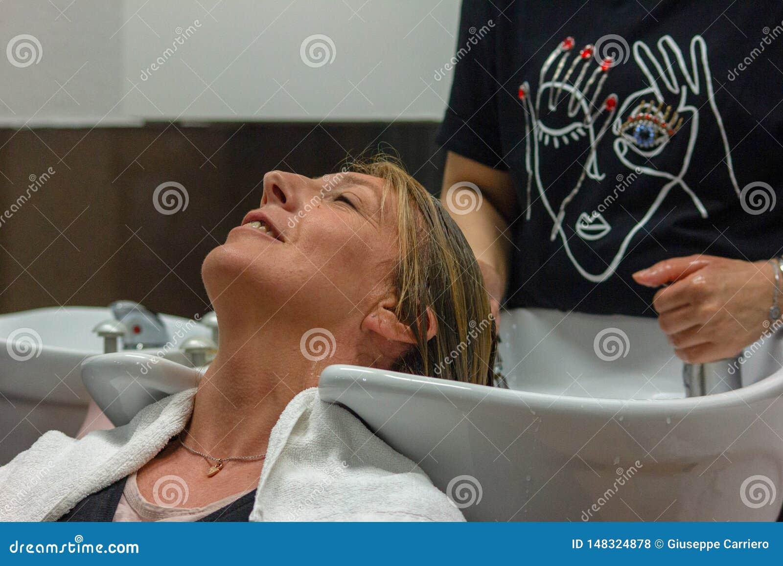 Detail van een woman& x27; s gezicht terwijl zij bij hairdresser& x27 is; s die haar haar doen