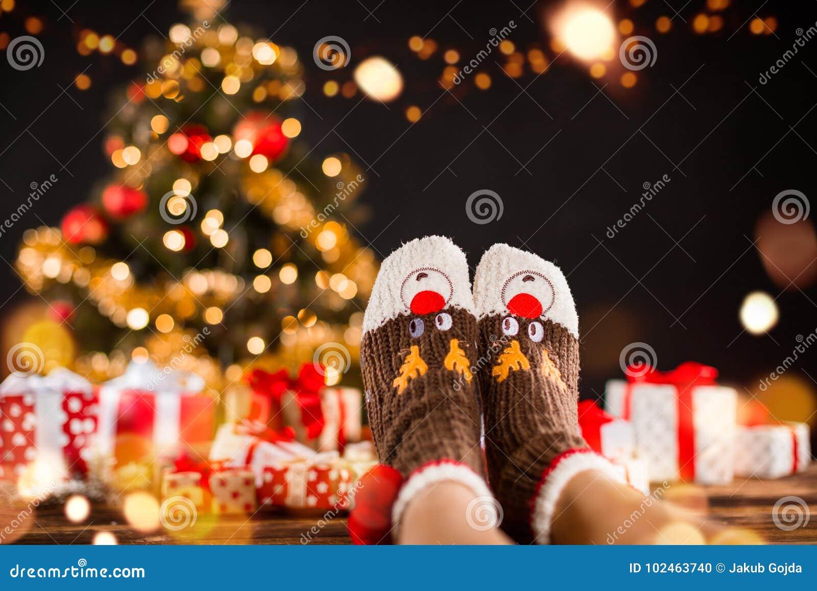 Detail van vrouwenbenen met gebreide sokken, Kerstboom met GIF