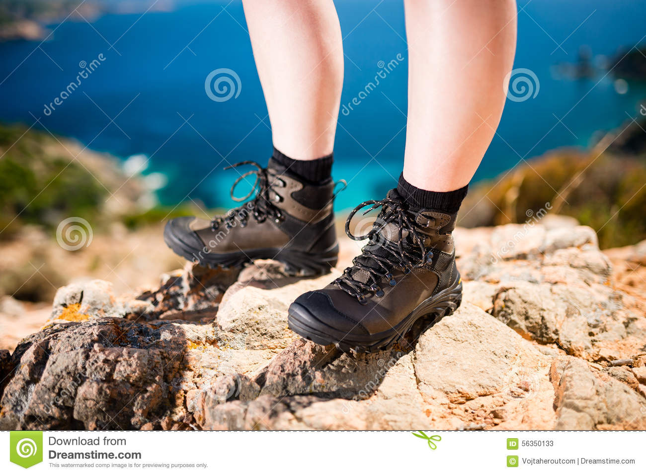Detail of women legs in brown leather trekking shoes standing on rock