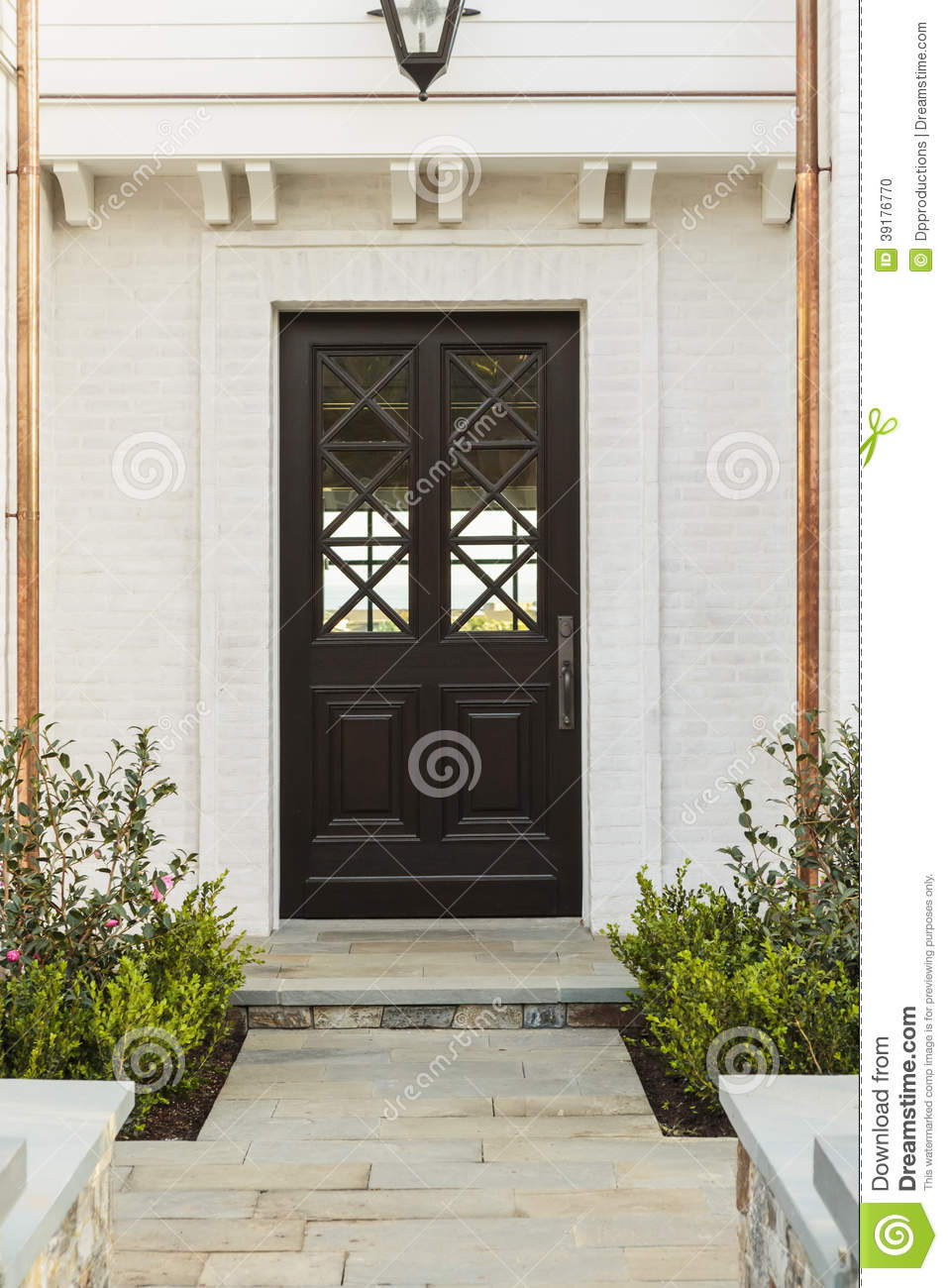 Detailed wooden front door of white brick home stock photo for White wooden front doors