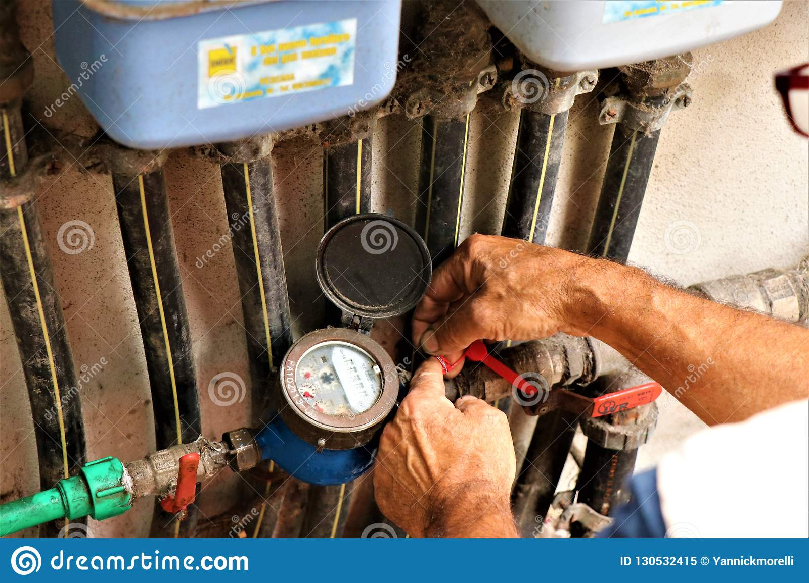 Details of a plumber intent on repairing a hydraulic valve.