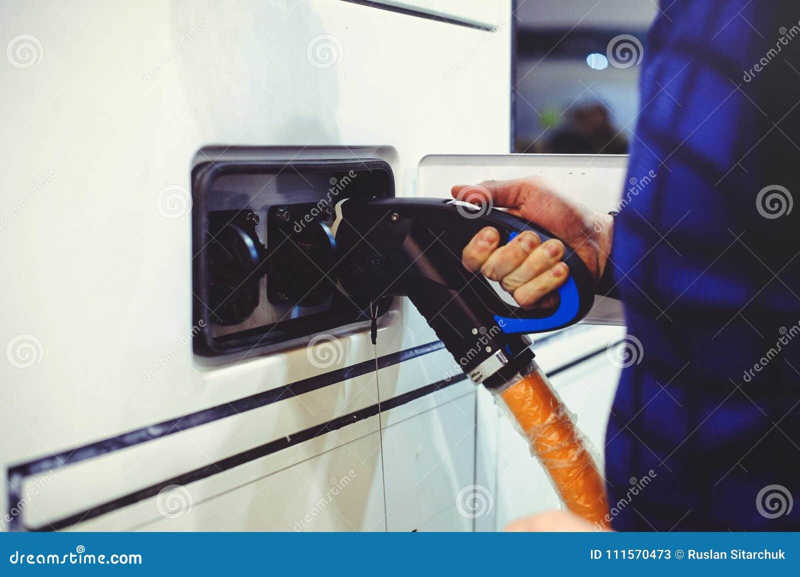 Details stadt-Bustransportes des Elektro-Mobils des Aufladungs Grün und erneuerbare Energiequellen Manngriffe in seiner Hand