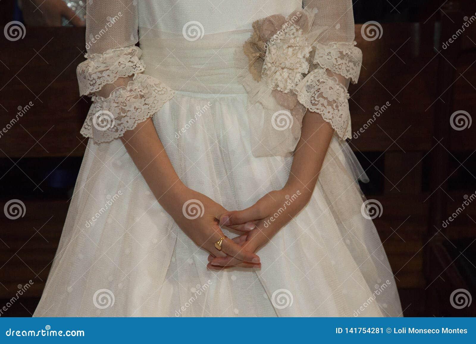Detalhe das mãos entrelaçadas de uma menina que esteja recebendo o primeiro comunhão