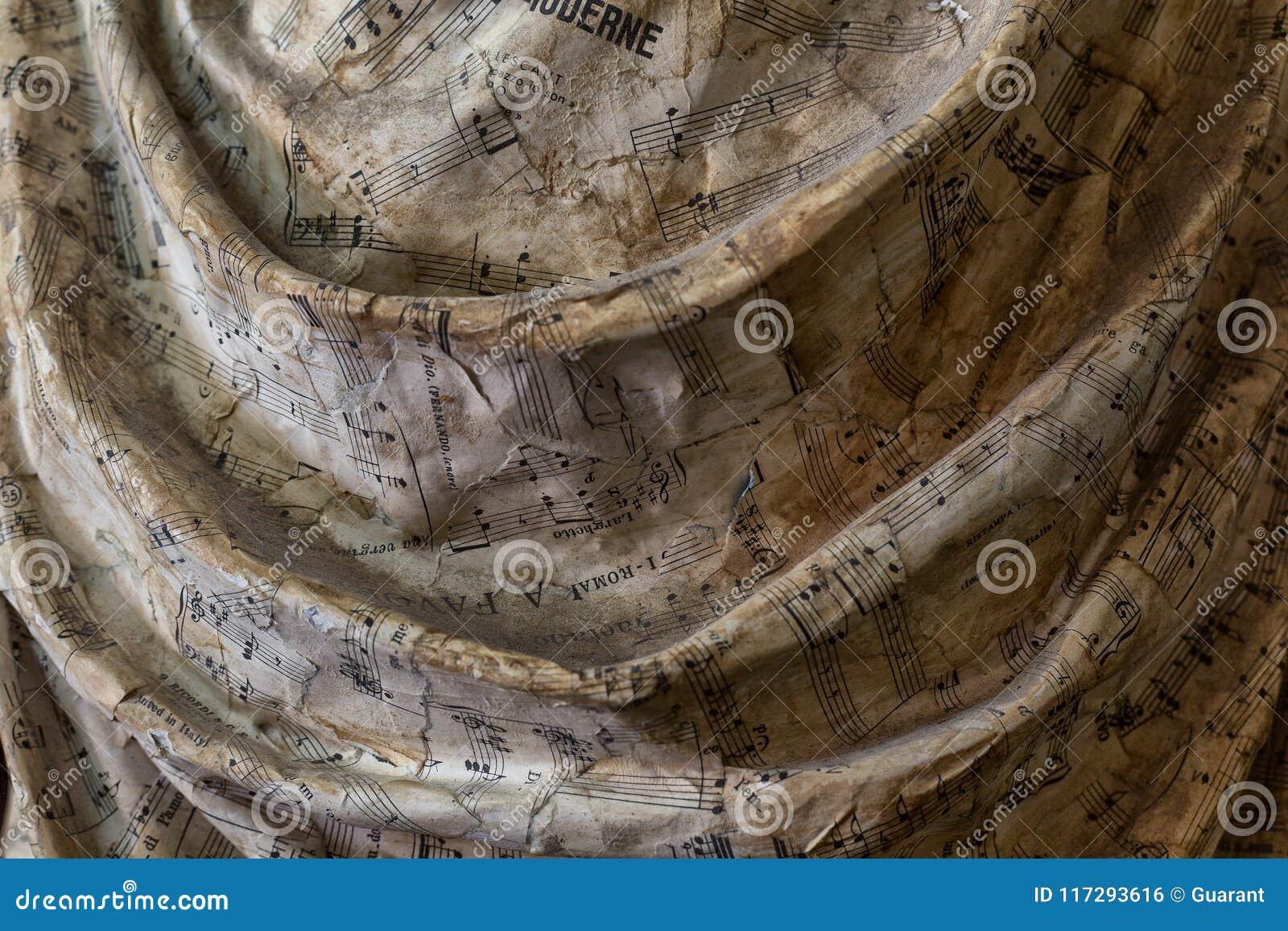 Detalhe de estátua com as dobras do vestido com notas musicais tiradas