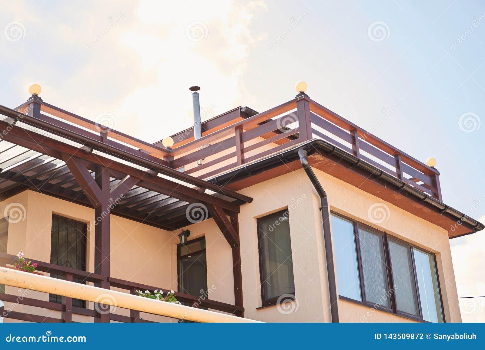 Detalhe do close-up de parte superior ecol?gica moderna nova da casa da casa de campo com o telhado marrom shingled no fundo do c