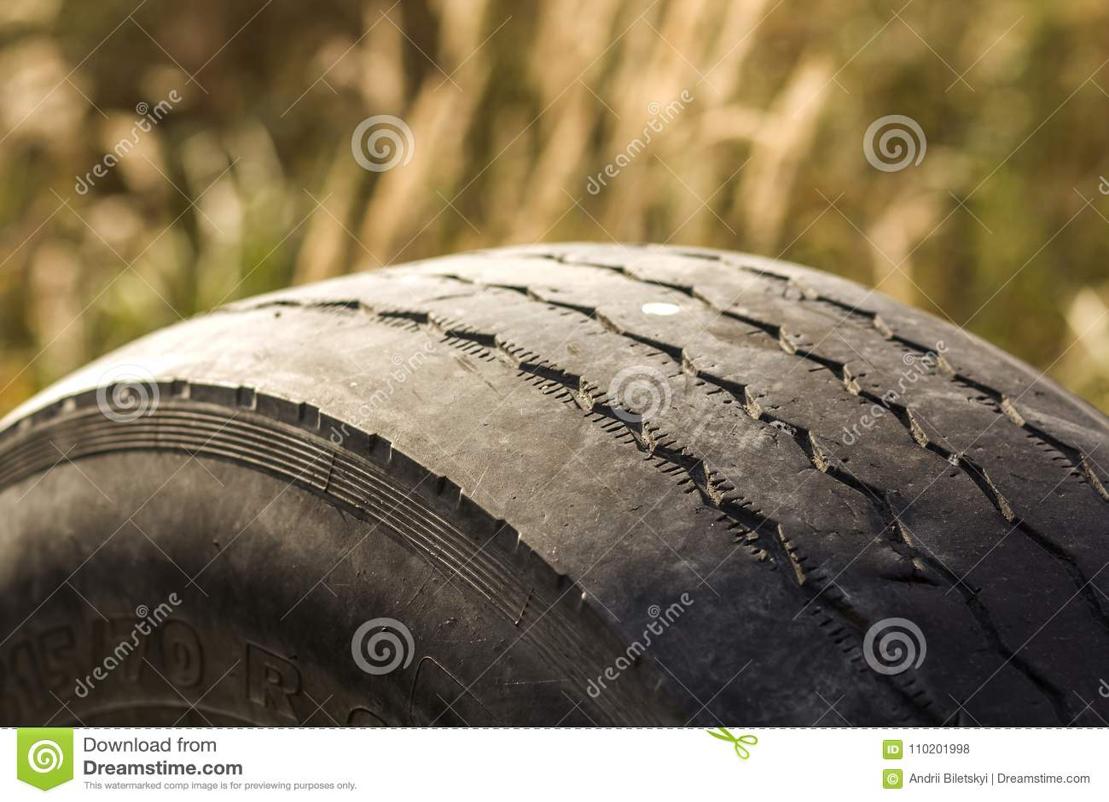 Detalhe do close-up de pneu da roda de carro vestido mal e calvo devido ao seguimento dos pobres ou ao alinhamento das rodas
