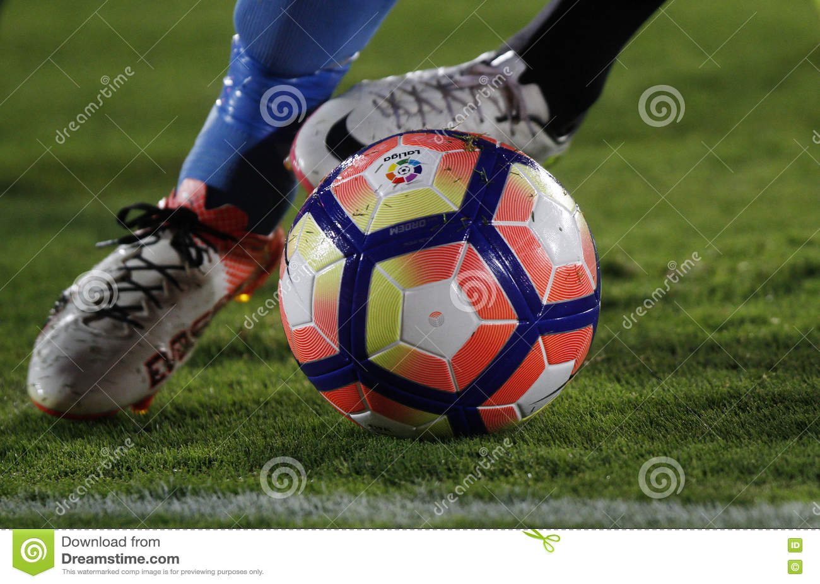 Detalhe dos pés de um jogador de futebol que corre com a bola