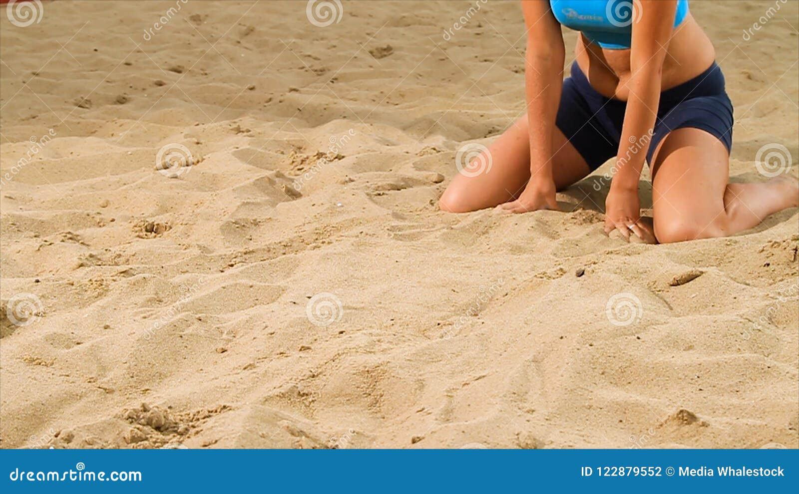 Detalj av den kvinnliga spelaren för volleyboll på stranden plats Närbild av en kvinna på sanden som spelar strandvolleyboll