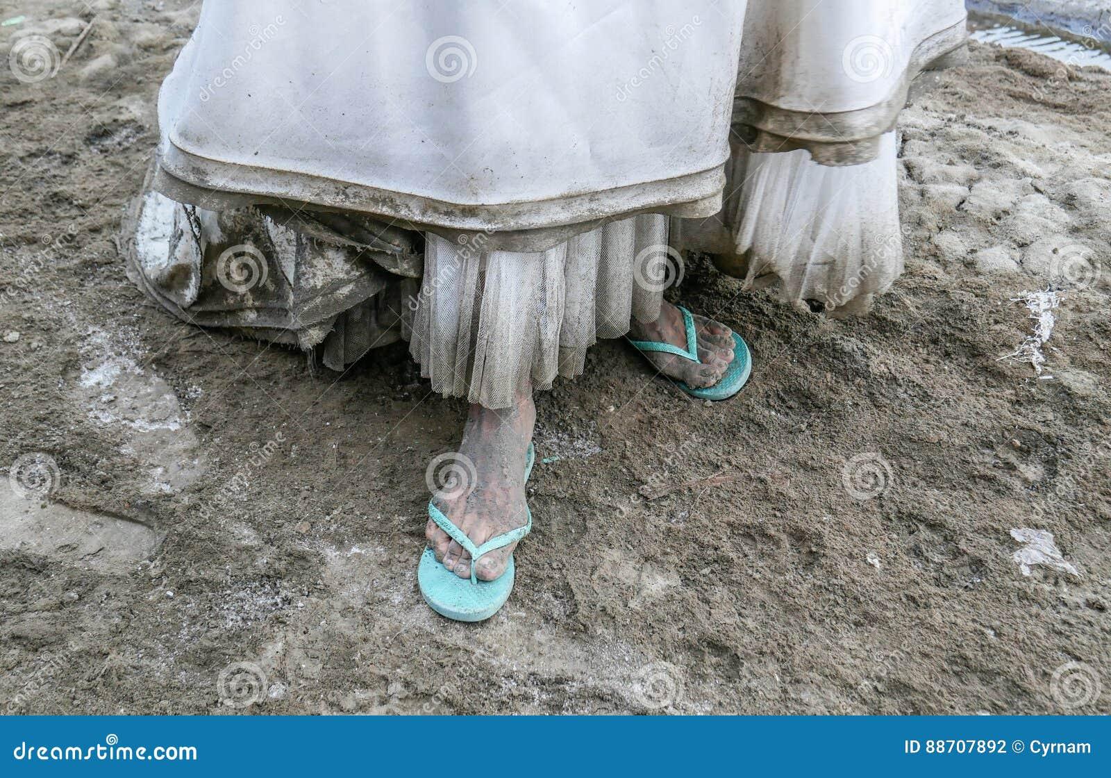 Detalj av den smutsiga vita bröllopsklänningen och nedsmutsade foten som täckas av gyttja och smuts