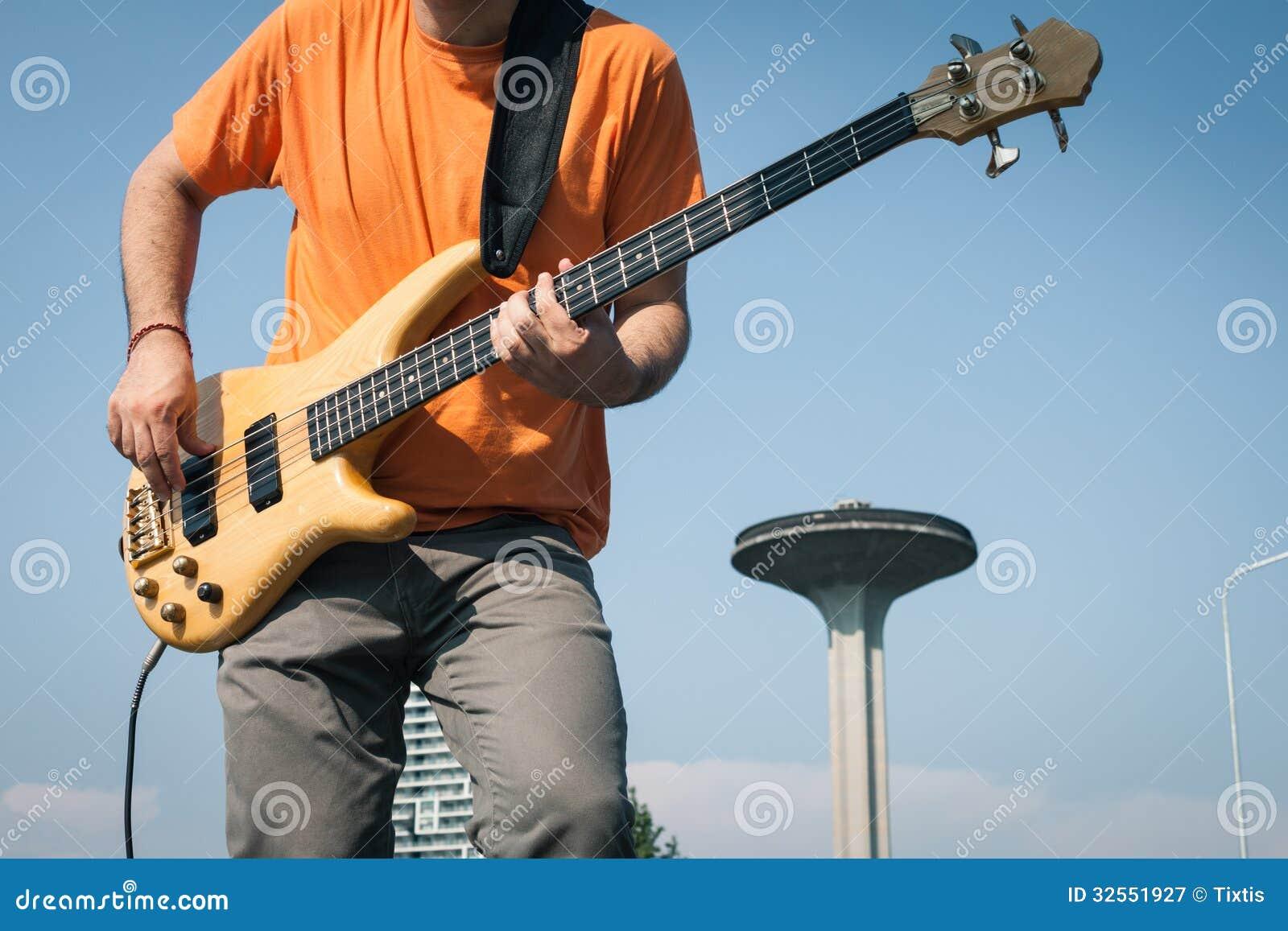 Detalj av en ung musiker som spelar elbasen
