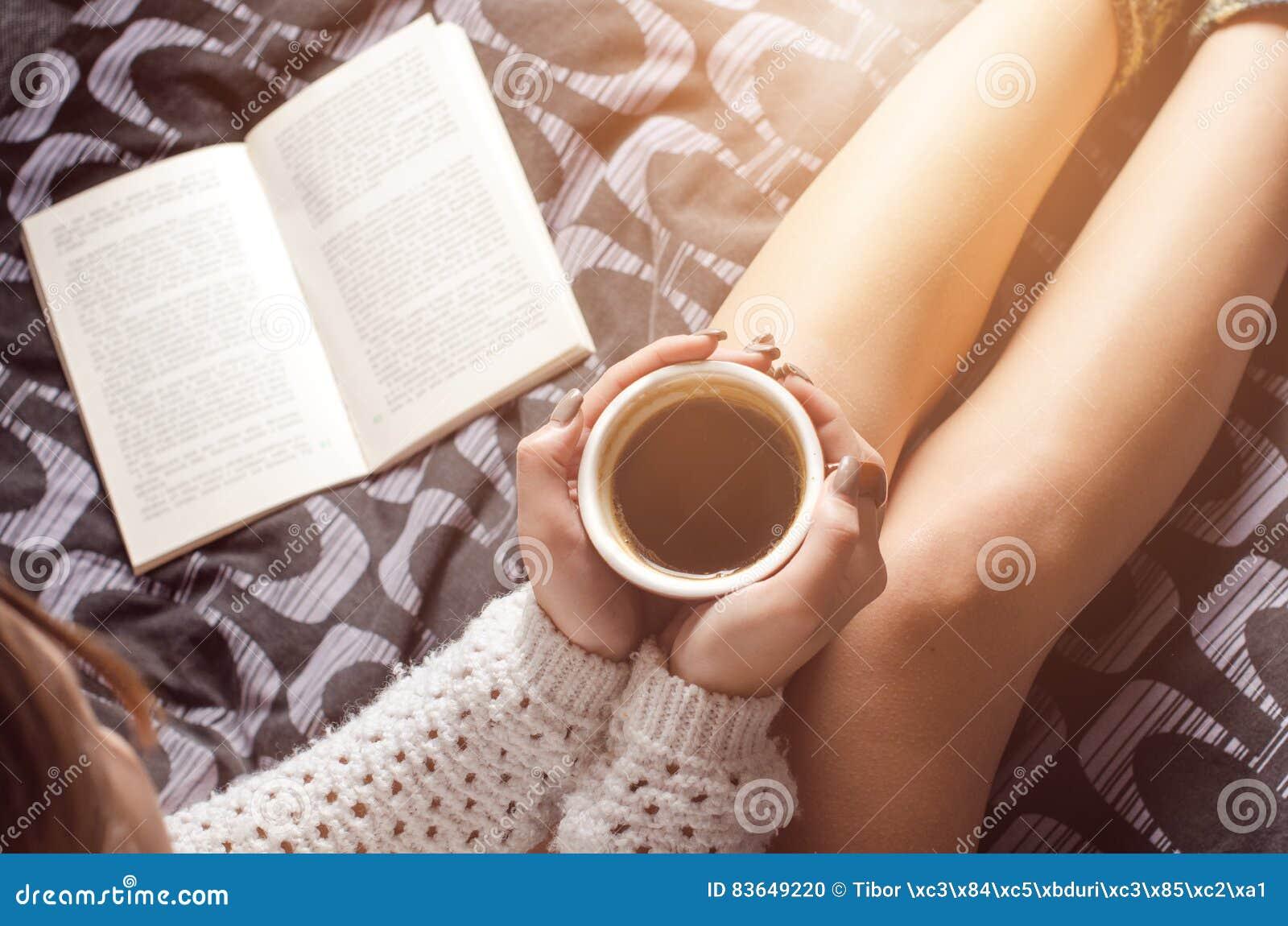 Detaljen av den sexiga unga kvinnan och solen tänder Kvinnauppehälle per kaffekoppen och läst en bok