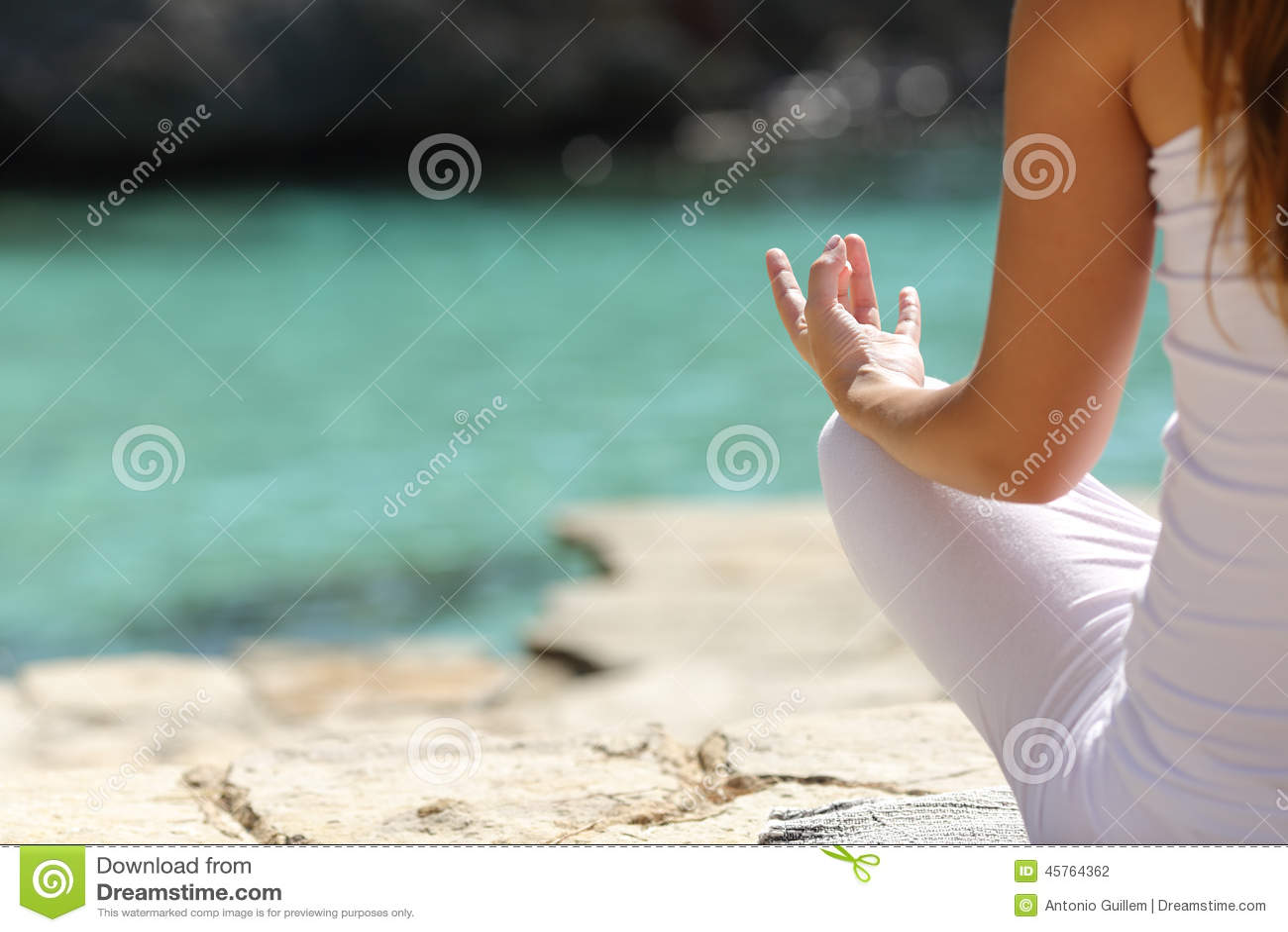 Detaljen av en kvinnahand som gör yoga, övar på stranden