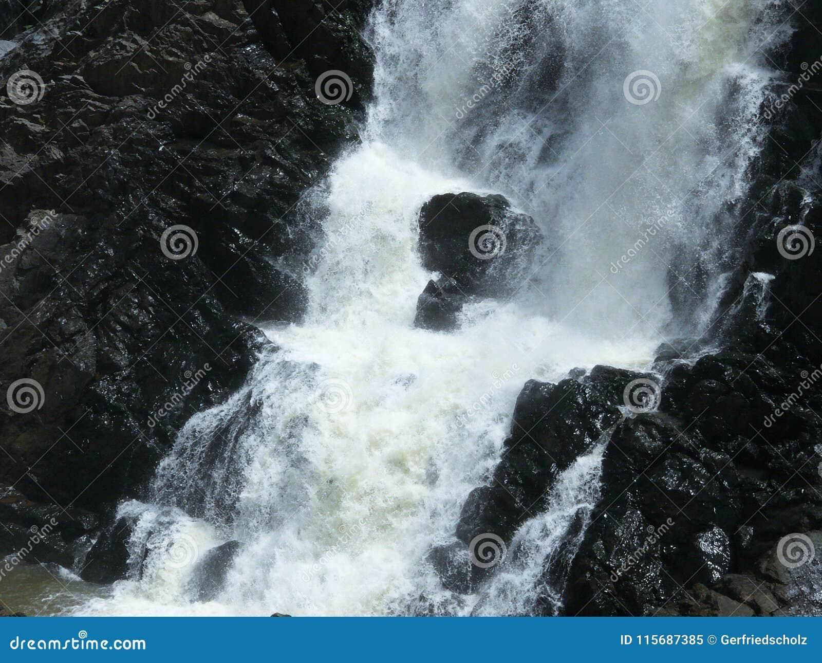 Detaljen av en vattenfall, vattnet kraschar ner vaggar