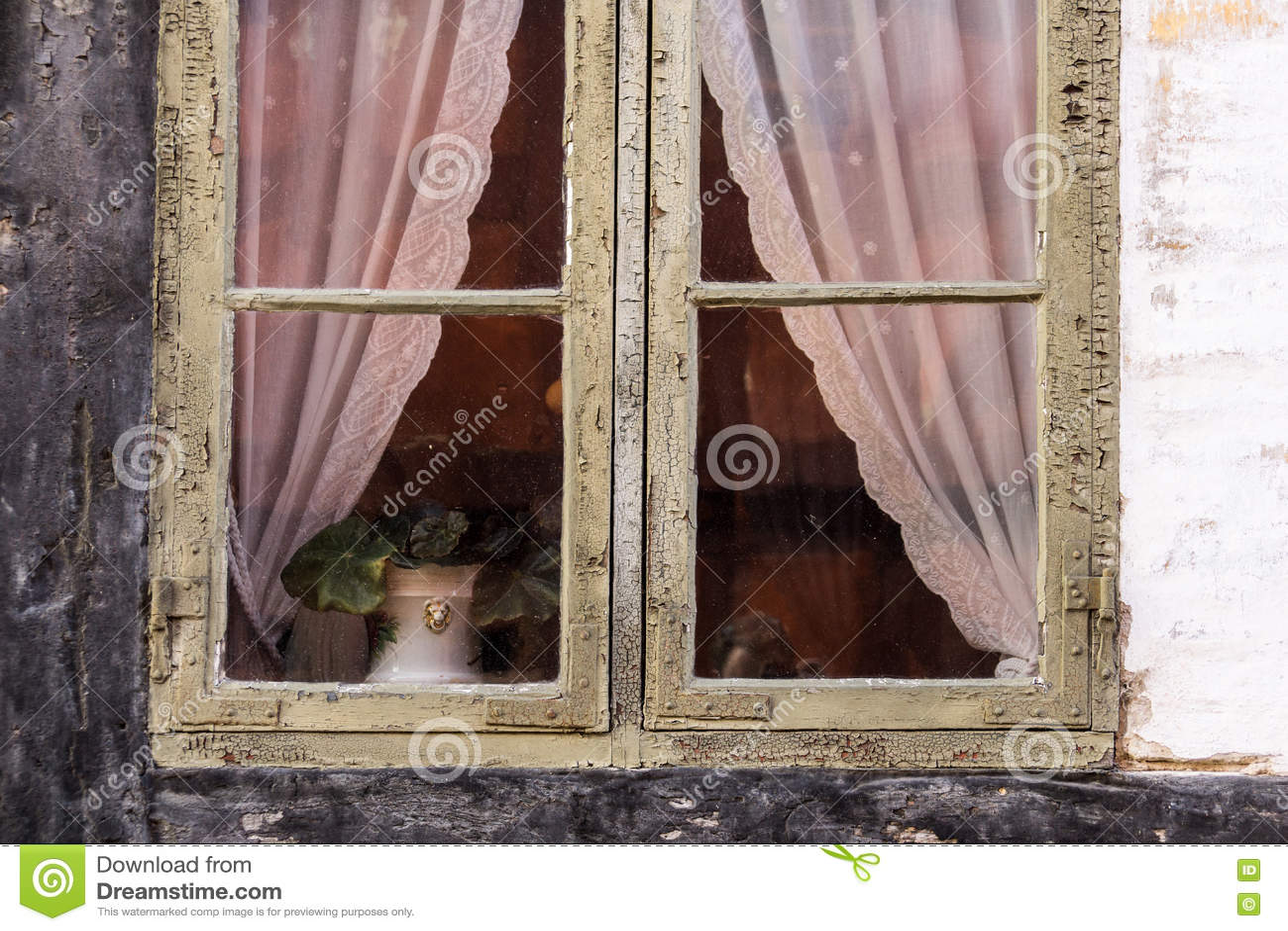 detalle de la ventana retra vieja con las grietas y los visillos