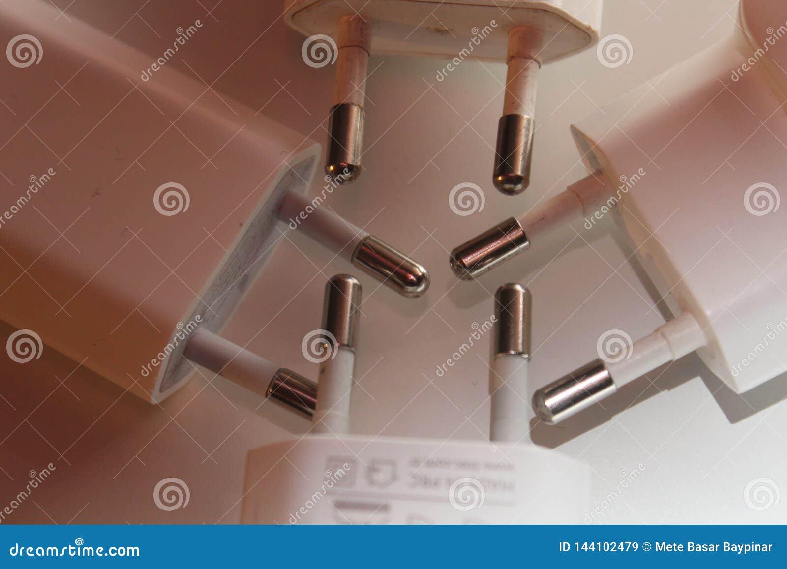 Detalle de las extremidades de los cargadores USB usados que se encuentran en el fondo blanco