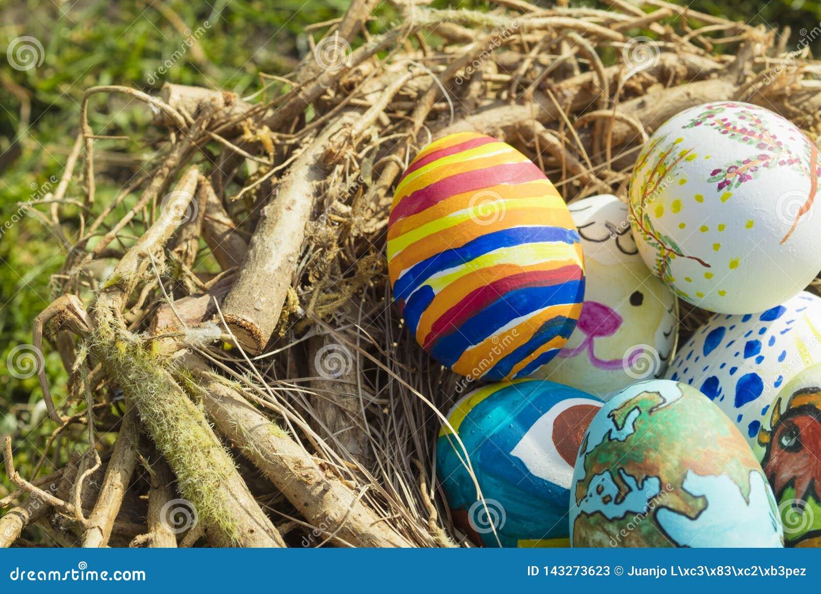 Detalle de los huevos de Pascua pintados con diversas formas, las historietas y los colores brillantes puestos en una jerarquía d