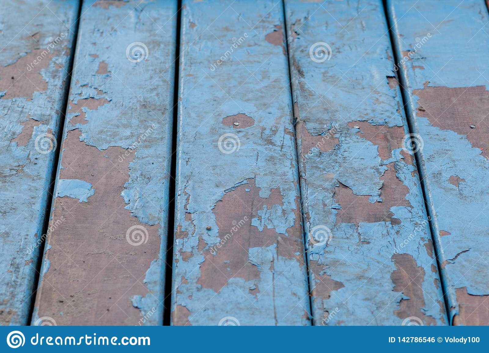 Detalle de los viejos tableros de madera pintados en azul claro con varias capas de pintura descascada