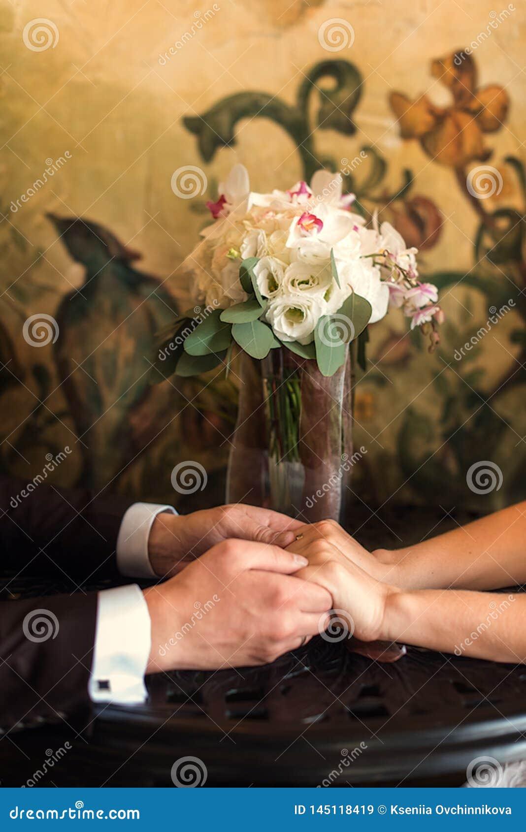 Detalle de sostenerse del ramo y de las manos de las rosas del ` s de la novia