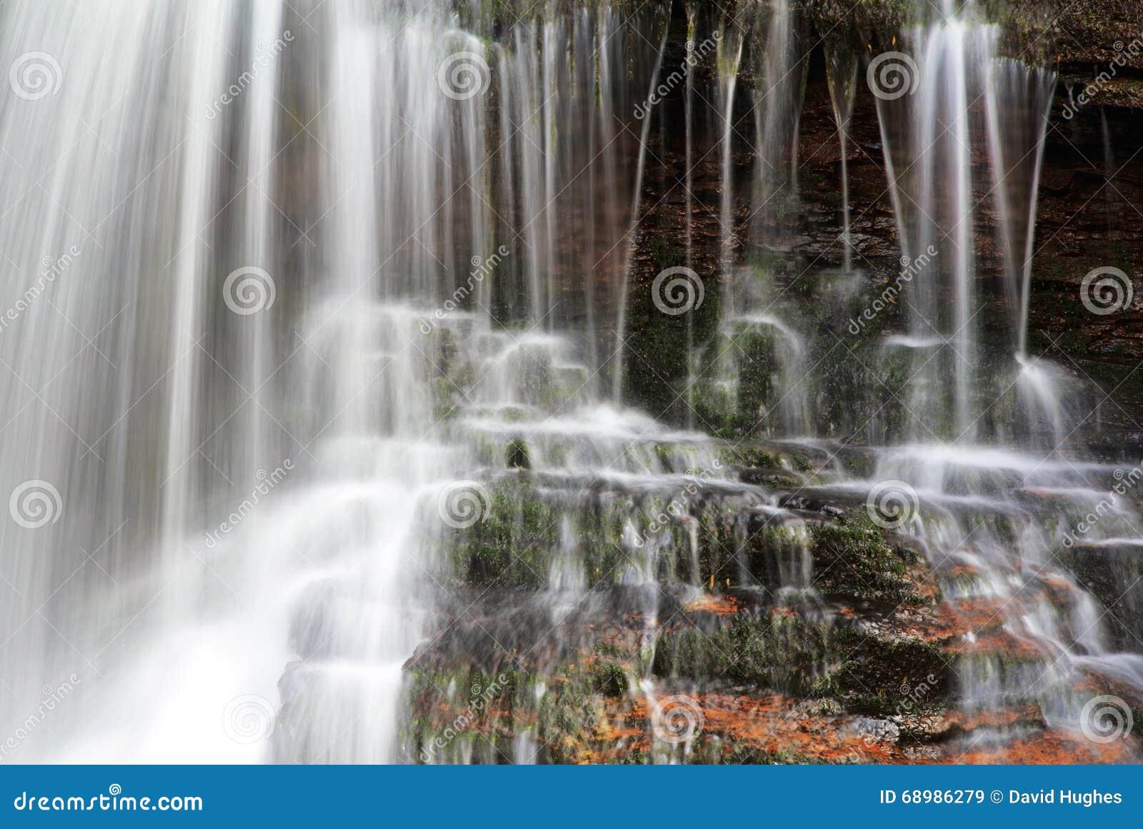 Detalle del agua borrosa que cae sobre musgo y roca roja