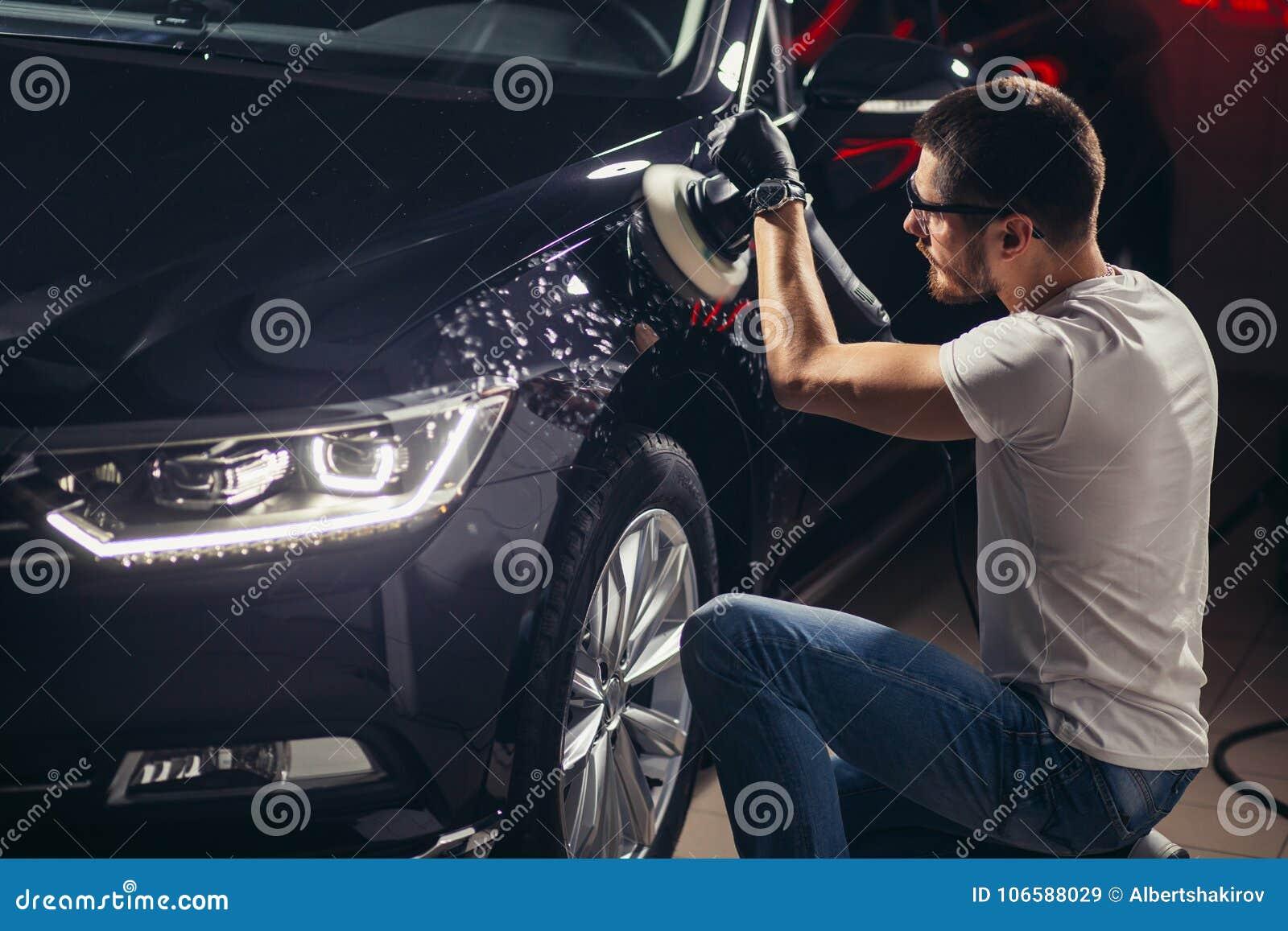 Detalle del coche - hombre con el pulidor orbital en taller de reparaciones auto Foco selectivo