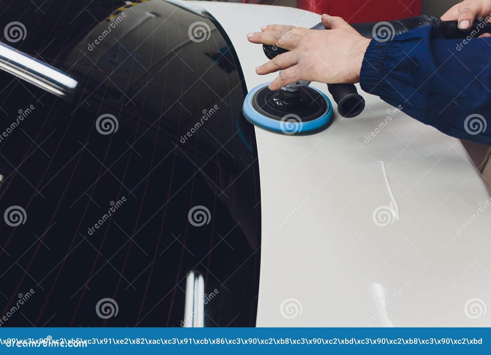 Detalle del coche - manos con el pulidor orbital en taller de reparaciones auto Foco selectivo