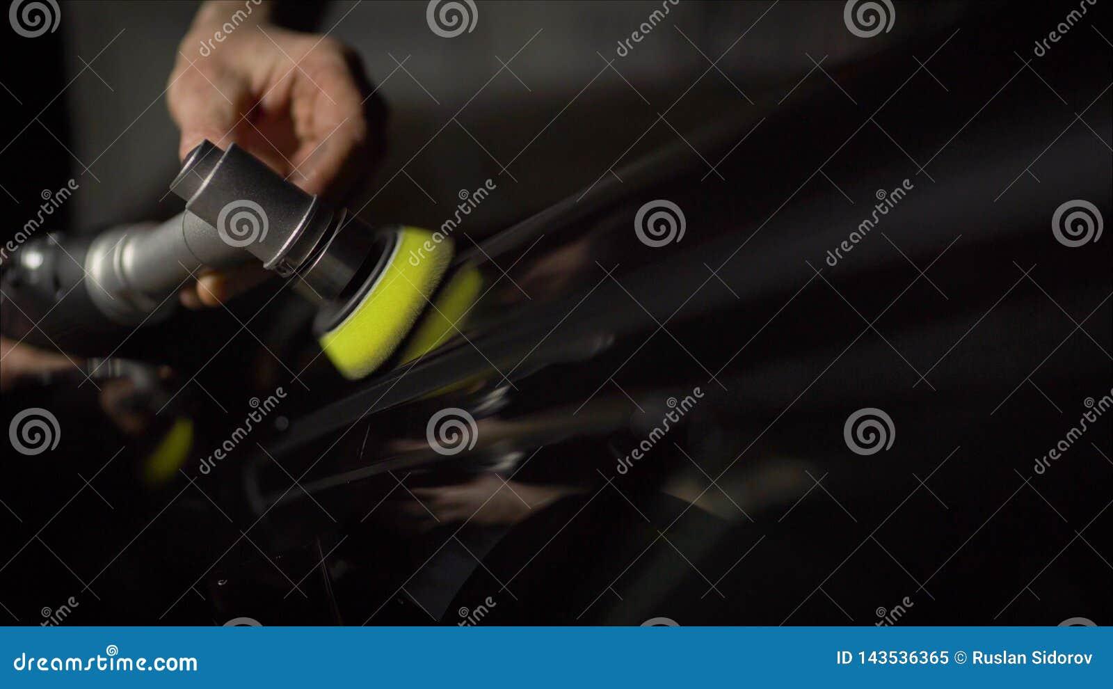 Detalle del coche - manos con el pulidor orbital en taller de reparaciones auto Foco selectivo Pulido del coche y correcci?n de L