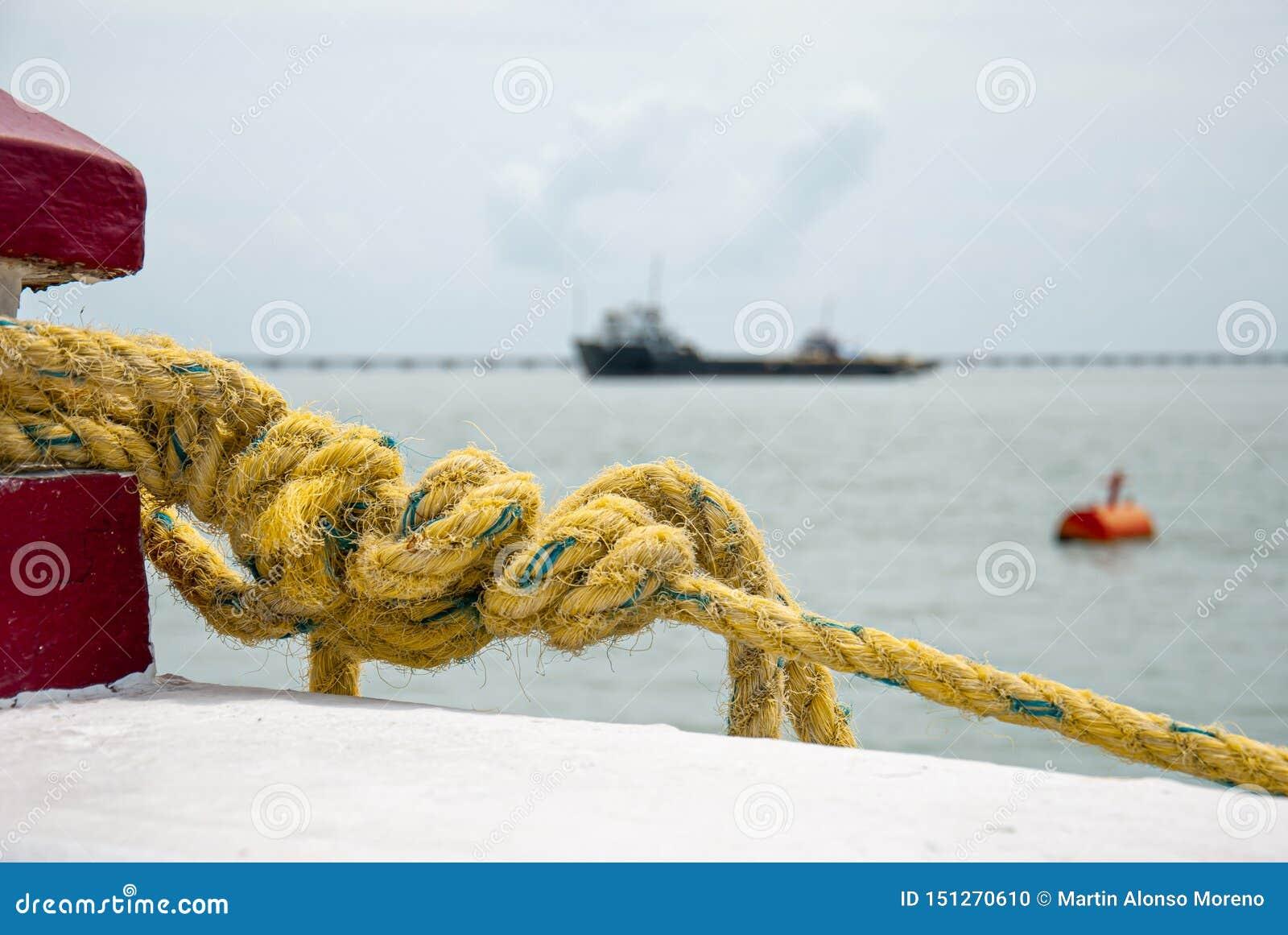 Detalle del primer de la cuerda atado a la ayuda náutica para sostener un barco
