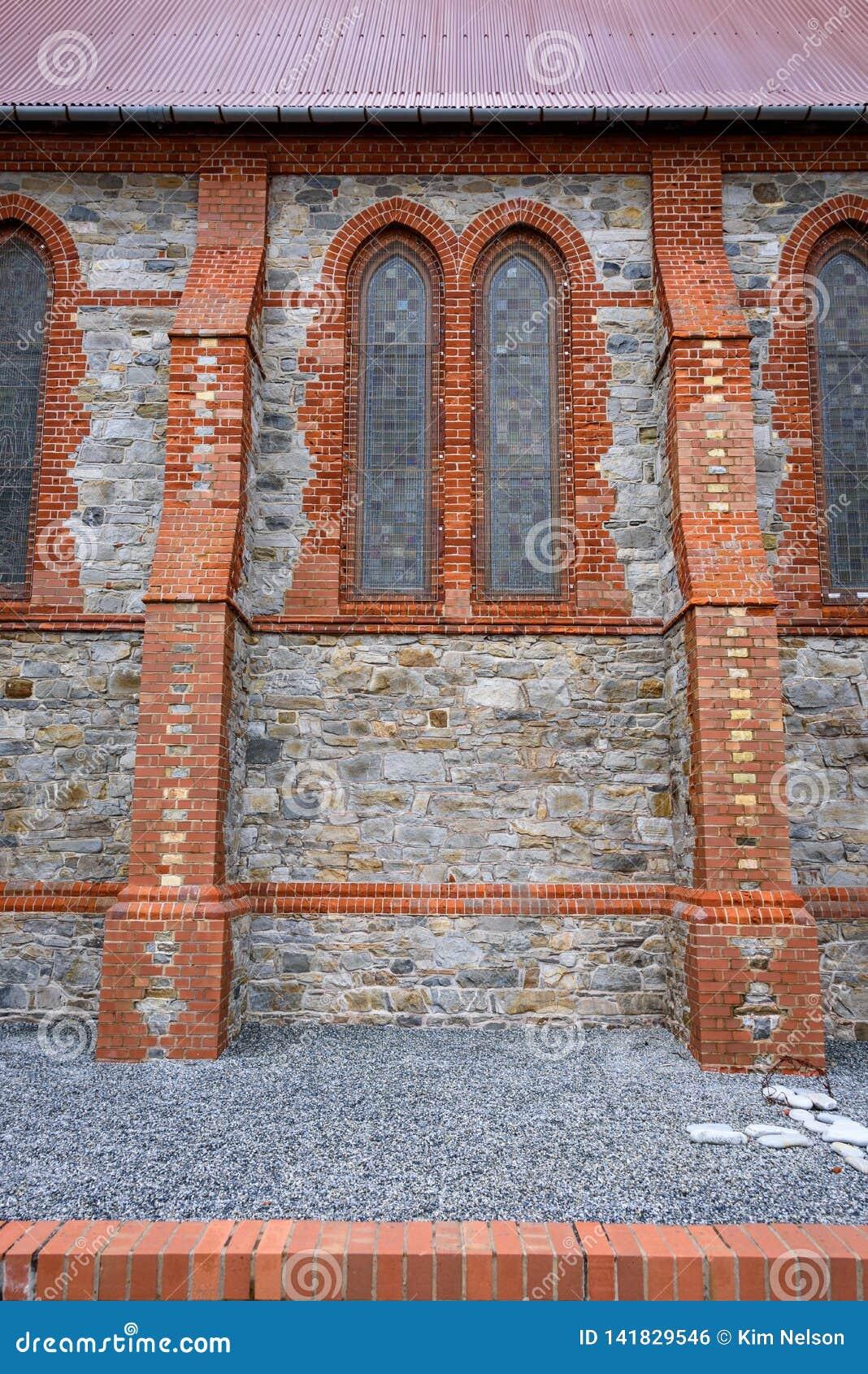 Detalle exterior de la piedra y del ladrillo de la catedral de la iglesia de Cristo, ventanas de vidrio de la mancha, tejado rojo