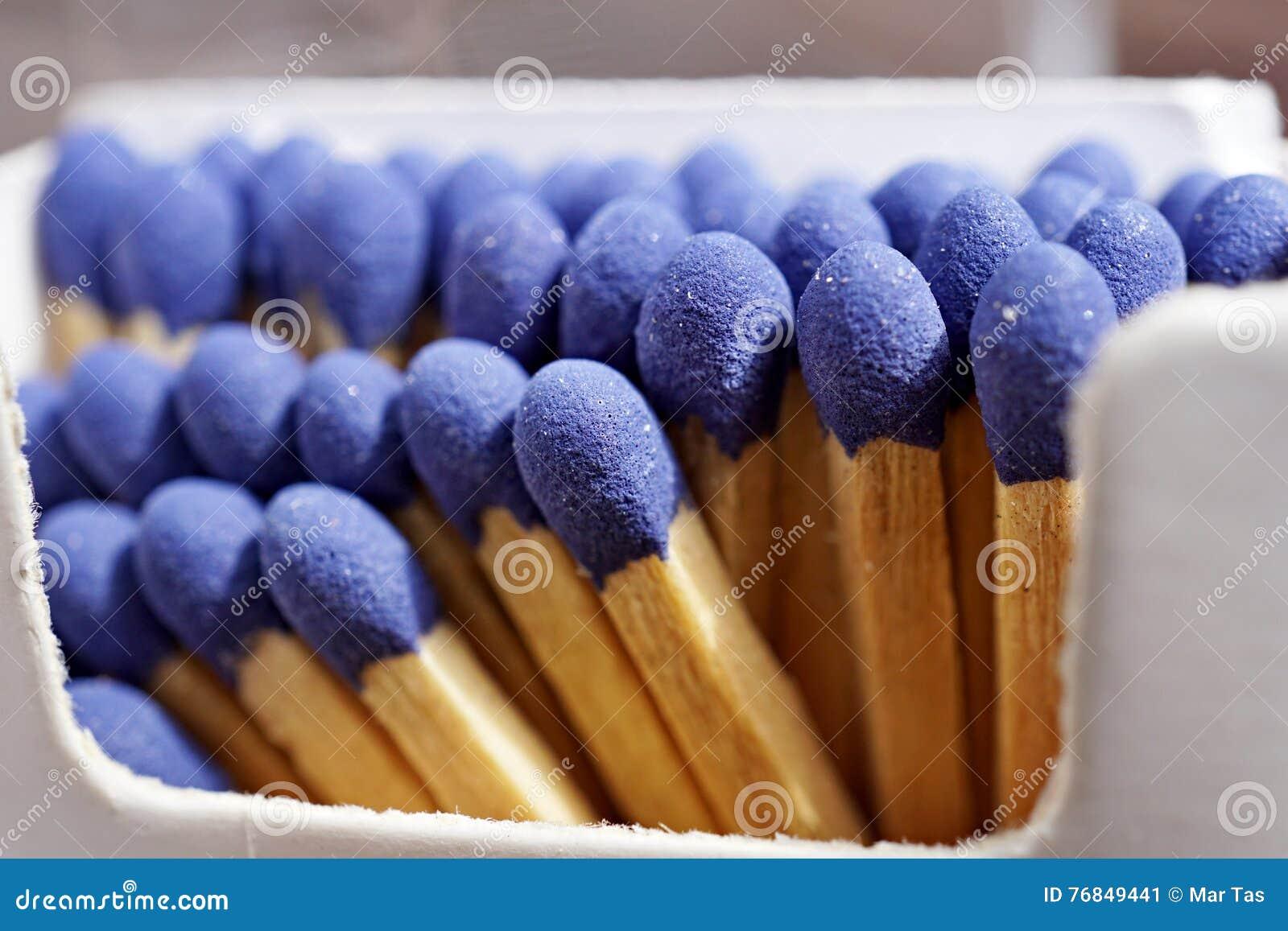 Detalle macro de los palillos del partido de seguridad con las cabezas azules en la caja del partido y el x28 de papel; matchbox&