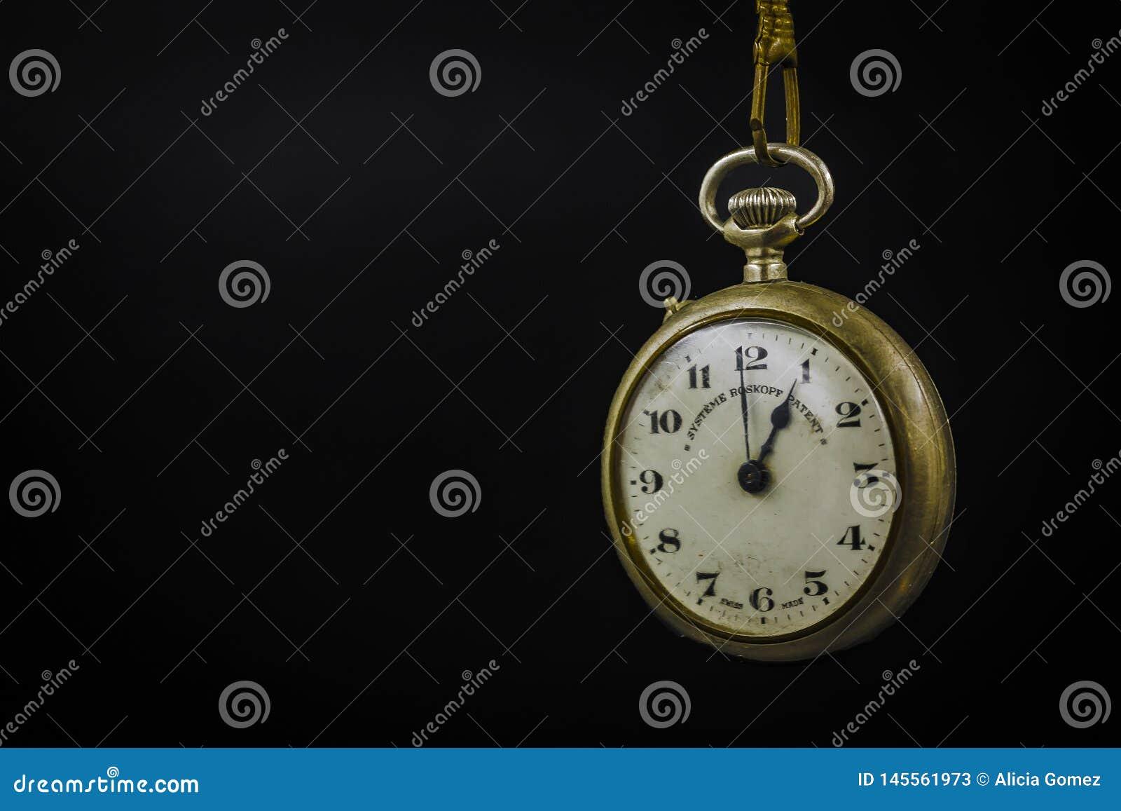 Detalle macro del reloj de bolsillo viejo del cromo del metal con la cadena