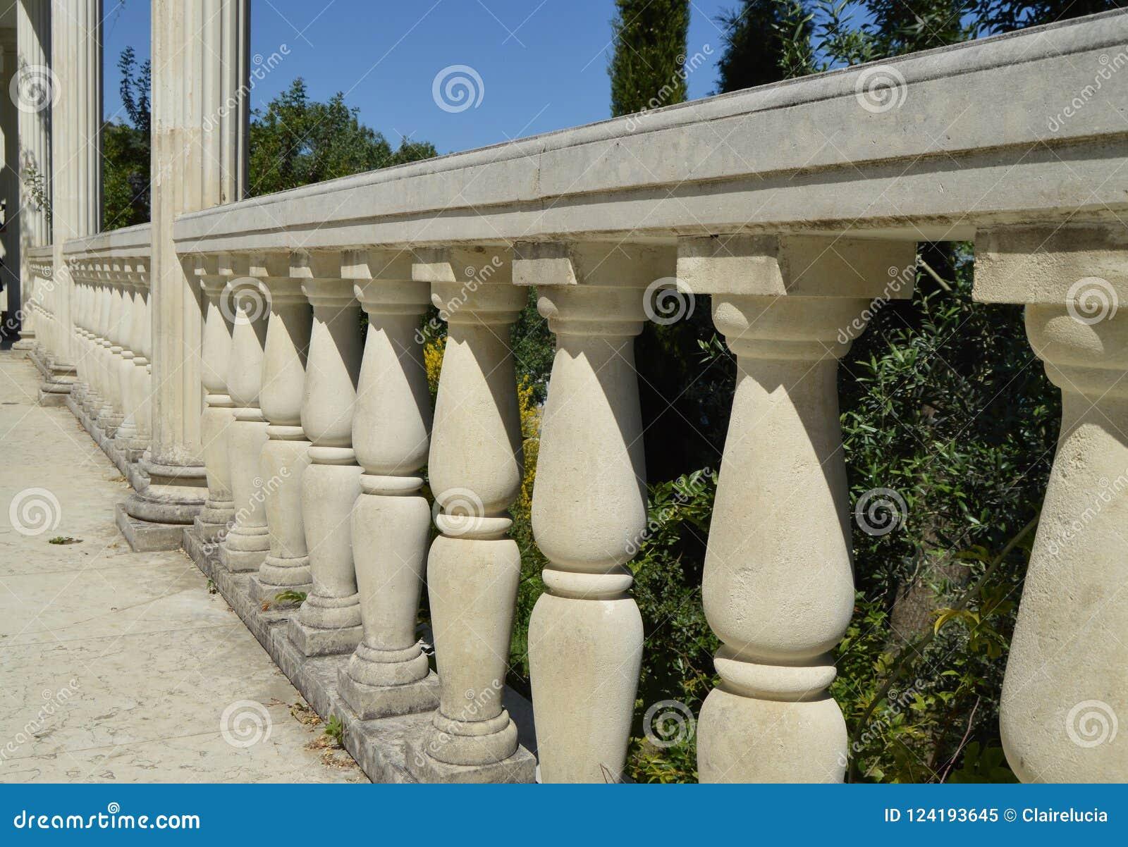Detalles de la barandilla, columnas de mármol blancas del primer, iluminadas por el sol